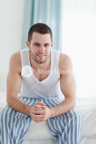 Portrait of a quiet man sitting on his bed