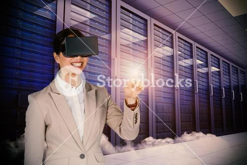 Composite image of smiling businesswoman pointing while wearing virtual video glasses