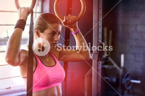 Young woman holding gymnastic rings in gym