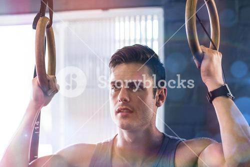 Close up of young man using gymnastic rings in gym