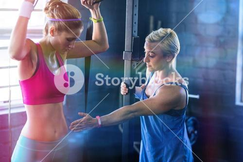 Female trainer instructing woman in gym