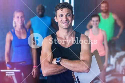 Portrait of smiling gym trainer holding clipboard