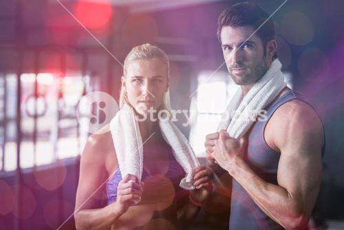 Portrait of serious friends with towel in gym