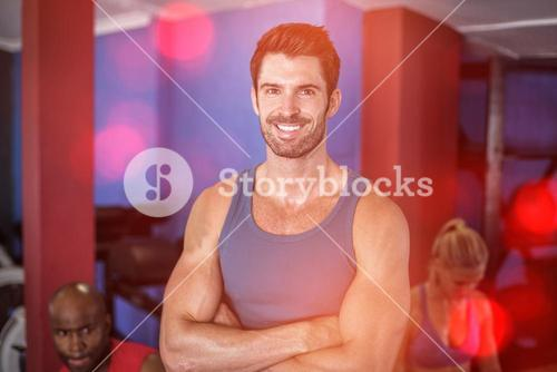 Portrait of smiling man with arms crossed in gym
