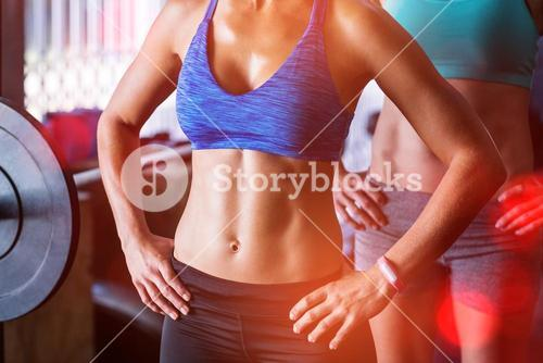 Midsection of female friends with hands on hip in gym