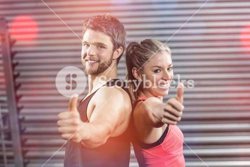 Portrait of serious couple standing back to back with thumbs up