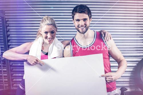 Fit couple holding blank paper