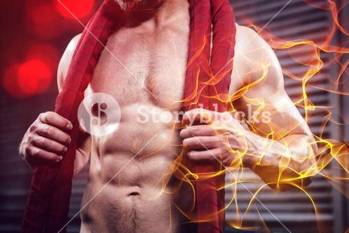 Midsection of shirtless man with battle rope around neck