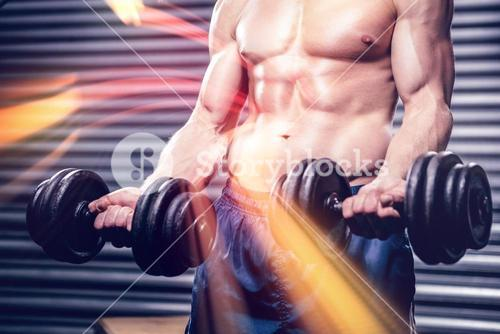 Midsection of shirtless man lifting heavy dumbbells