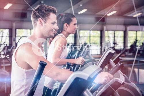 Beautiful woman and man exercising on elliptical machine