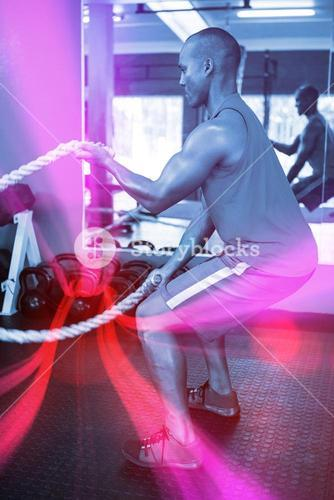 Side view of male athlete exercising with ropes