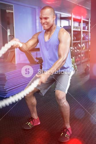 Athlete exercising with ropes in fitness studio