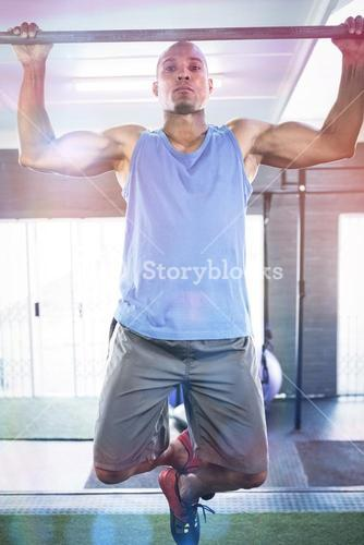 Portrait of male athlete doing chin-ups