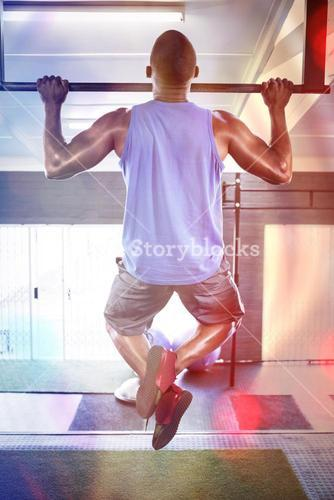 Male athlete doing chin-ups in fitness studio