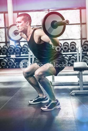 Muscular man exercising with barebell