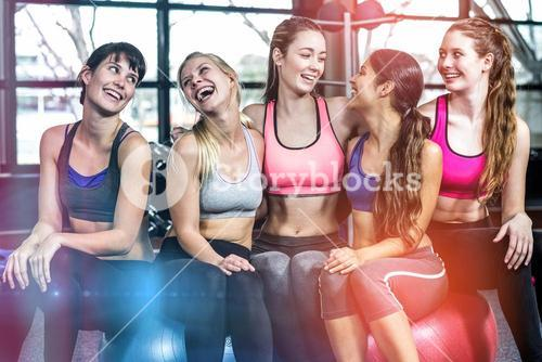 Group of fit woman smiling while sitting on exercise balls