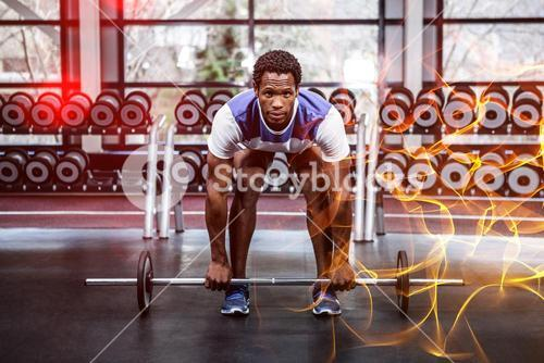 Concentrated muscular man lifting barebell