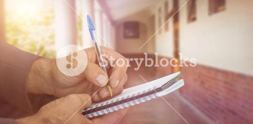 Composite image of close up of man writing in spiral book