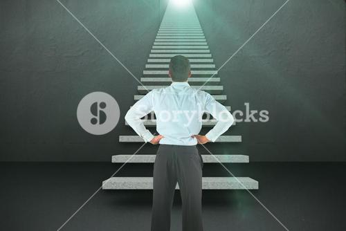 Composite image of businessman standing back to the camera with hands on hips 3d