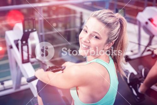 Fit woman on drawing machine