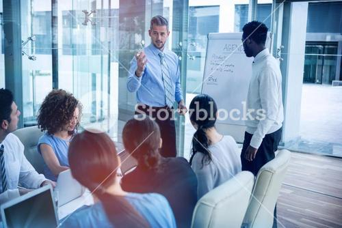 Businessman discussing on white board with coworkers