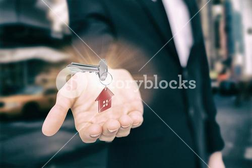 Composite image of close up of metallic key and red home keychain