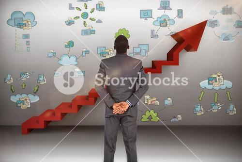 Composite image of young businessman standing with hands behind back