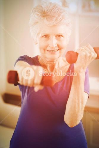 Portrait of senior woman exercising with dumbbells