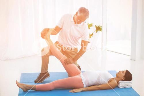 Physiotherapist stretching pregnant lady leg