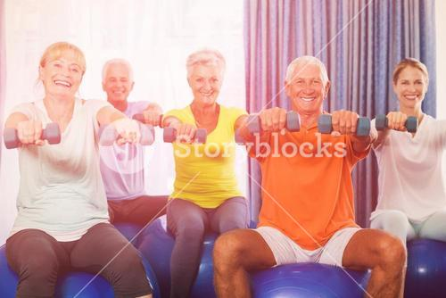 Portrait of seniors using exercise ball and weights
