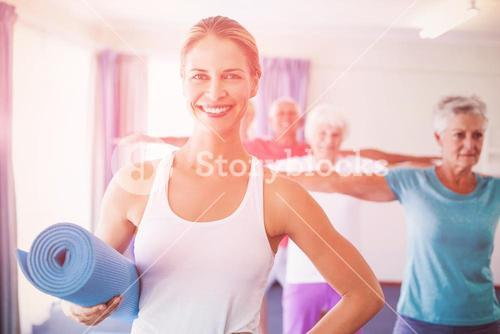 Portrait of Instructor holding yoga mat
