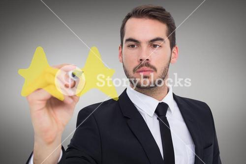 Composite image of focused businessman writing with marker