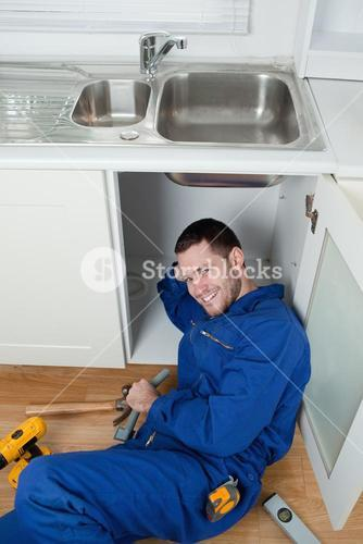 Portrait of a smiling repairman fixing a sink