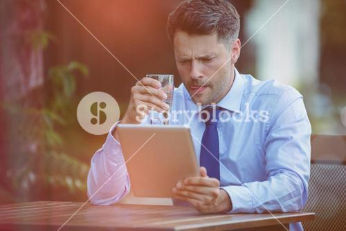 Businessman drinking water while using digital tablet