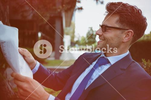 Cheerful businessman reading newspaper in yard