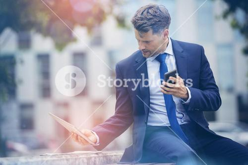 Businessman holding mobile phone while using digital tablet on retaining wall
