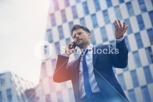 Low angle view of business man gesturing while speaking on mobile phone