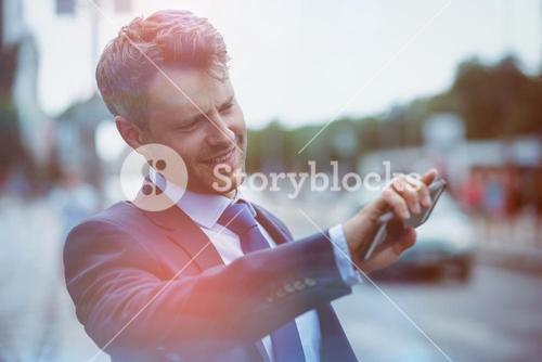 Handsome businessman holding mobile phone and hailing taxi