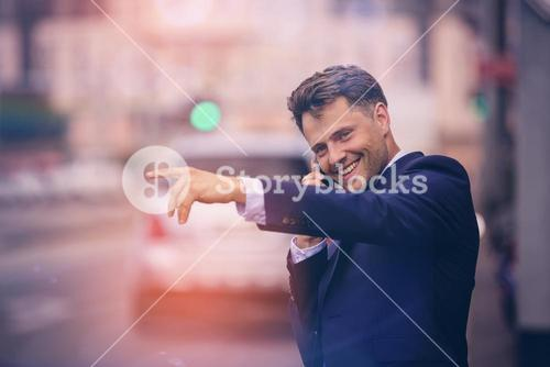 Handsome businessman hailing taxi while taking on phone
