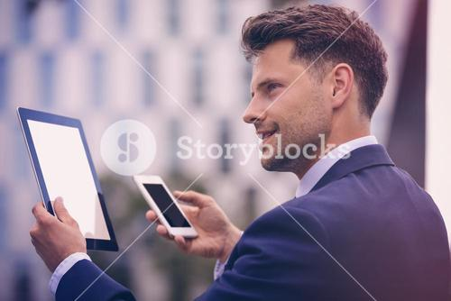 Businessman using digital tablet and mobile phone