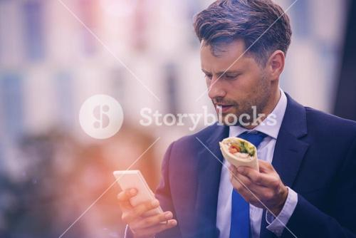 Handsome businessman holding mobile and snack