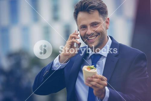 Handsome businessman holding wrapped sandwich while talking on mobile phone