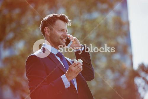 Handsome businessman holding food while talking on mobile phone