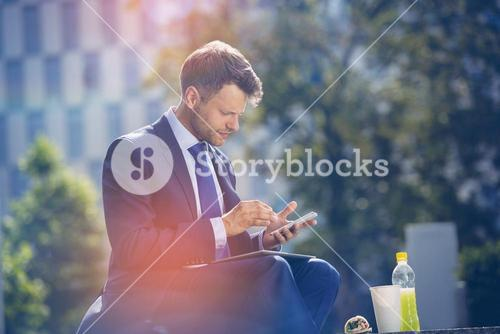 Handsome businessman using mobile phone with food and drink on table