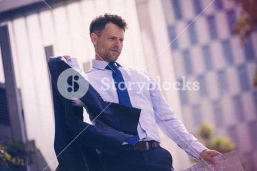 Low angle view of Businessman holding blazer and newspaper