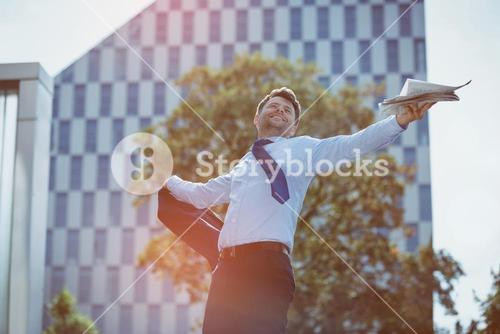 Carefree businessman holding blazer and newspaper