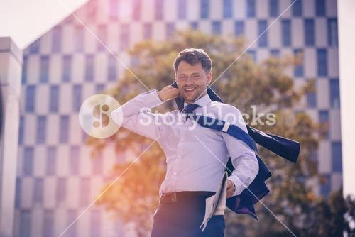 Cheerful businessman holding blazer and newspaper