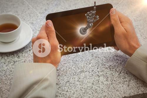 Composite image of businessman holding small tablet at table 3d