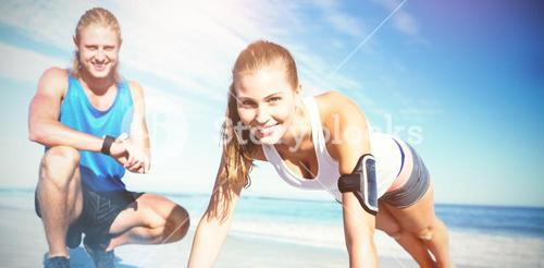 Portrait of couple exercising on sand