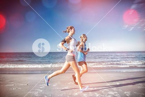 Side view of friends jogging at beach